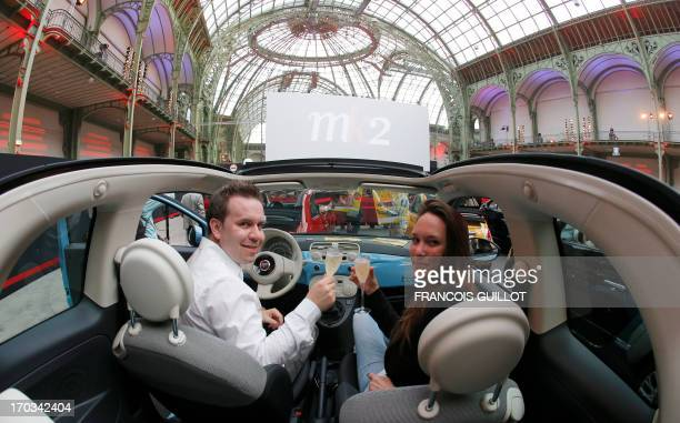 A couple has glasses of champagne in an Italian car prior to the projection of The Big Lebowski at the Grand Palais in Paris on June 11 during the...