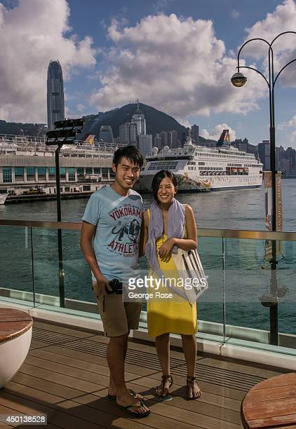 A couple has their picture taken in front of a large passenger cruise ship docked in Kowloon on May 24 in Hong Kong China Viewed as the world's third...
