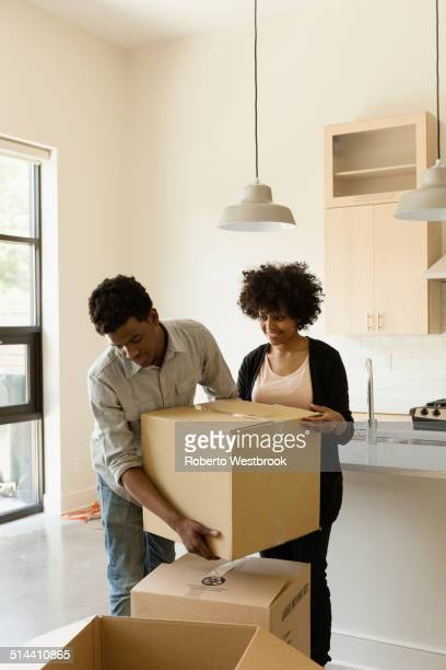 Couple hauling cardboard boxes in new house
