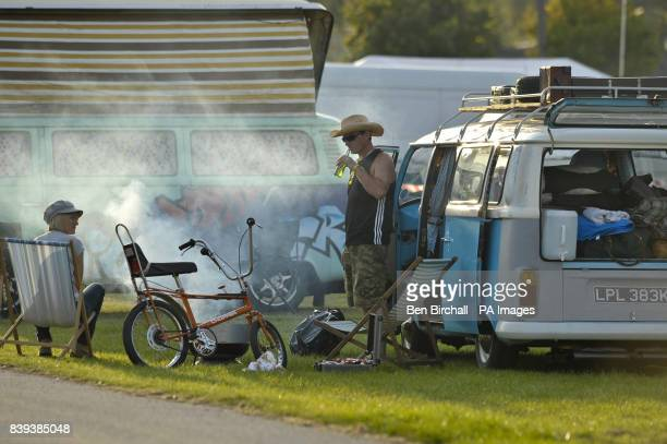 A couple have a barbeque at VW Baywindow Type 2 Transporter at Vanfest festival in the Three Counties Showground Malvern where thousands of VW...