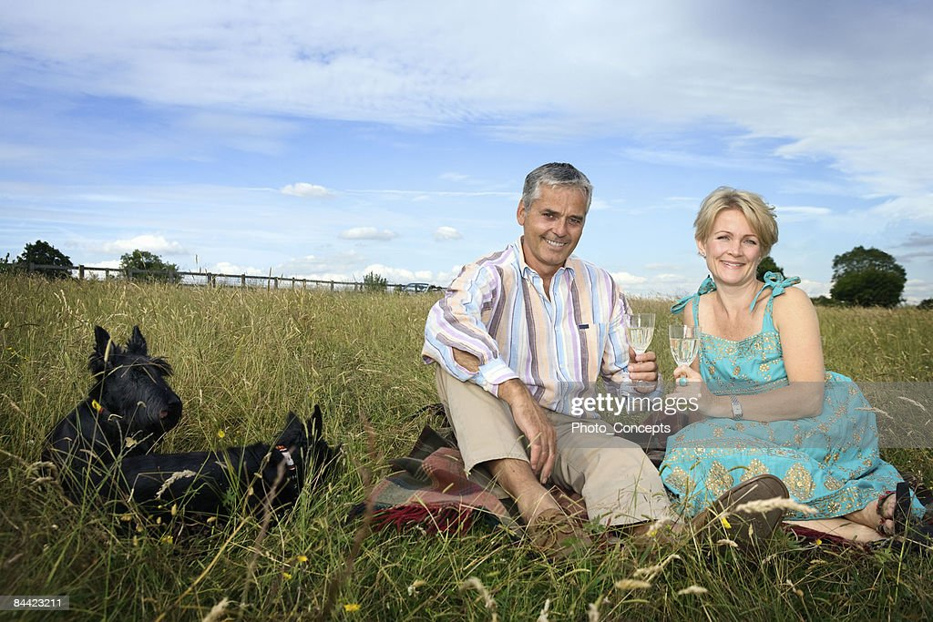 Couple have a picnic in a field : Stock Photo