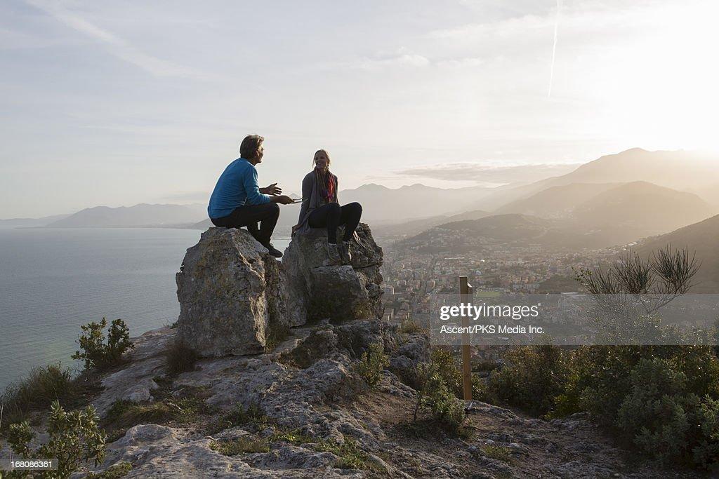 Couple have conversation on rocks, above sea