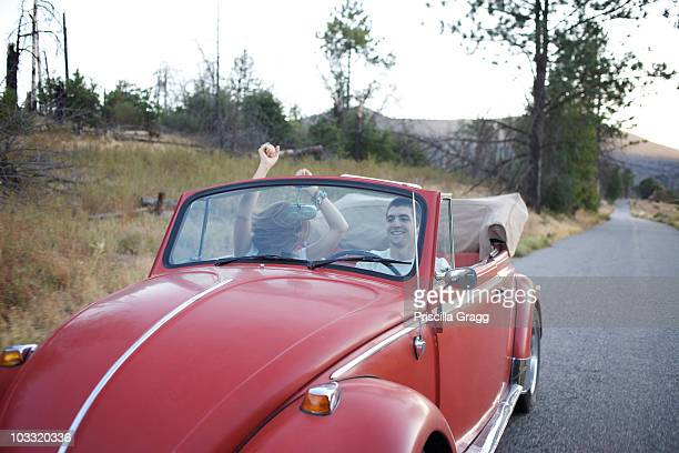 Couple have fun driving their retro car.