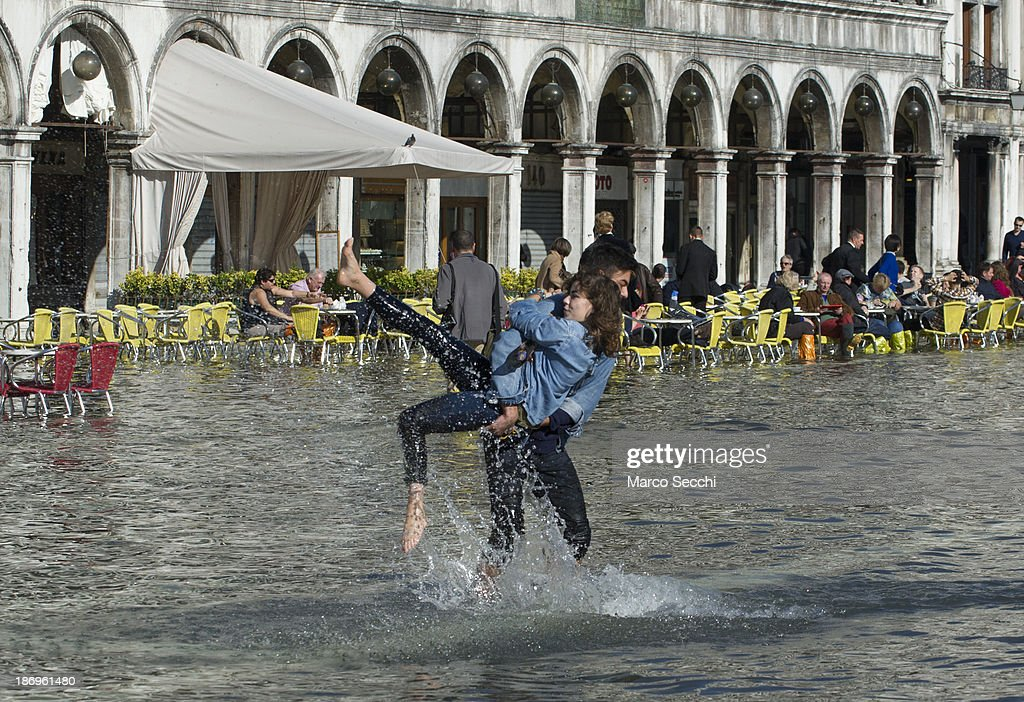 A couple have fun in Saint Mark's Square during today's Acqua Alta on November 5, 2013 in Venice, Italy. The high tide, or acqua alta as it is locally known, is a natural event most commonly affecting the city during Autumn and Winter.