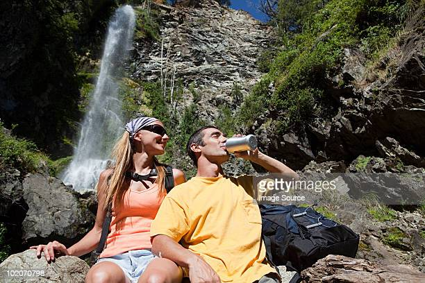 Couple having a drink by waterfall