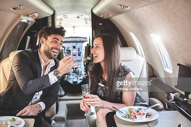 Couple having a meal inside jet airplane