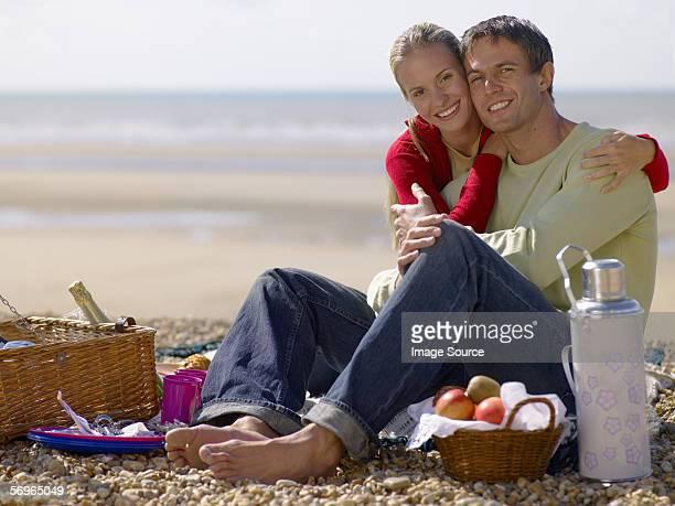 Couple ayant un pique-nique sur la plage