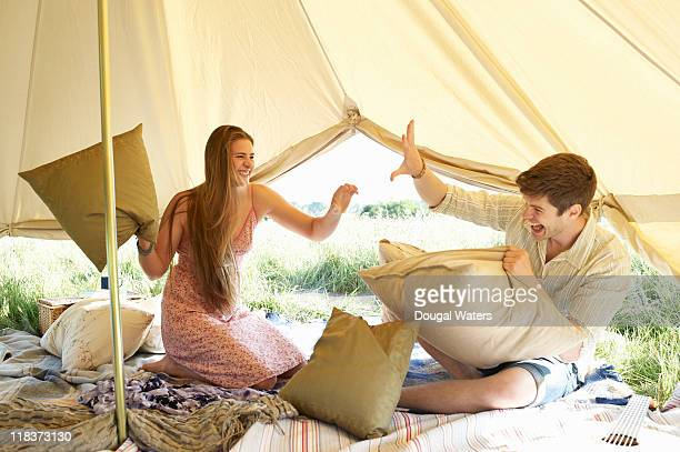 Couple having a pillow fight in tent.
