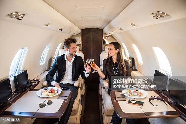 Couple having a toast inside jet airplane