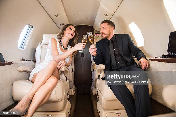 Couple having a toast inside private jet aeroplane
