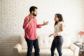Young hispanic couple having argument at home in the living room