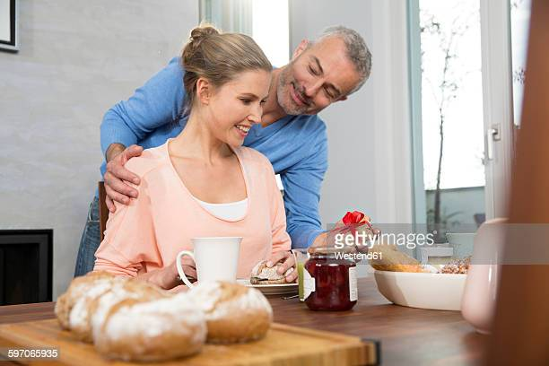 Couple having breakfast, man proposing with preasent