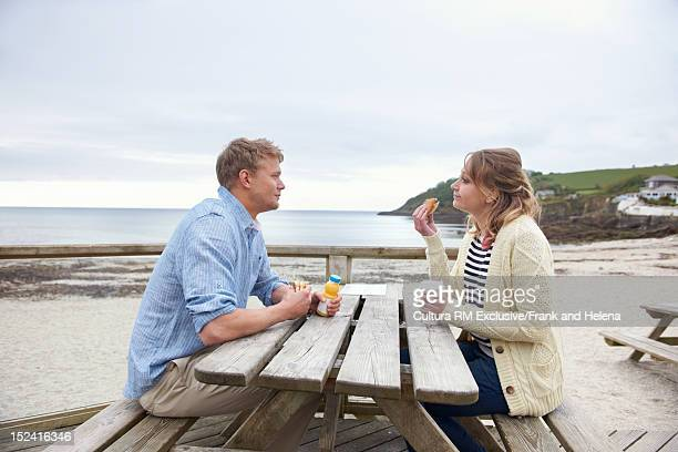 Couple having breakfast on beach