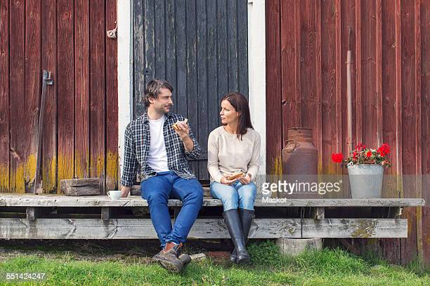Couple having breakfast while sitting outside barn at farm