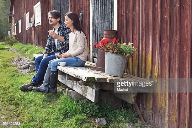Couple having breakfast while sitting outside barn at farm