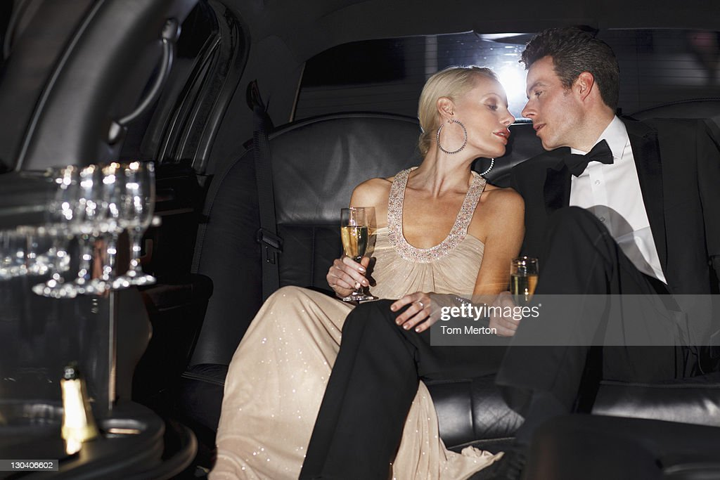 Couple having champagne in backseat of limo : Stock Photo