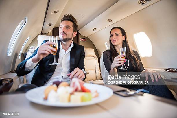 Couple having champagne inside jet airplane