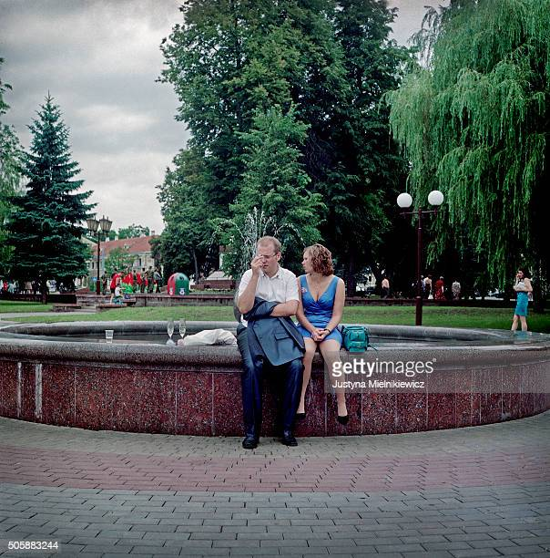 A couple having champagne on the fountain of the park which is a must stop for each newly married couple in Grodno on July 15 2011 in Grodno Belarus