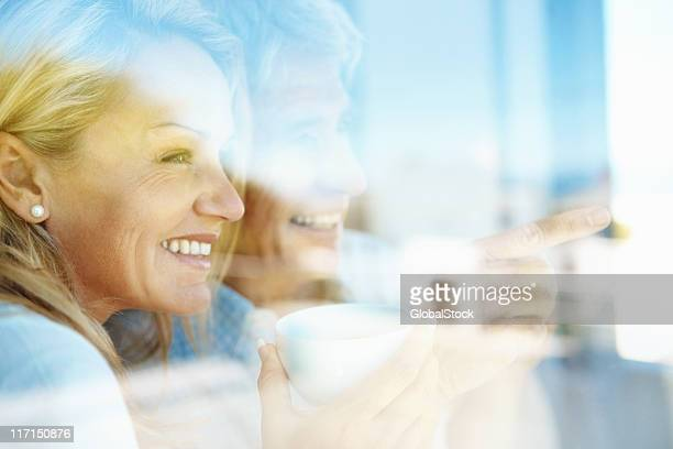 Couple having coffee and looking out the window
