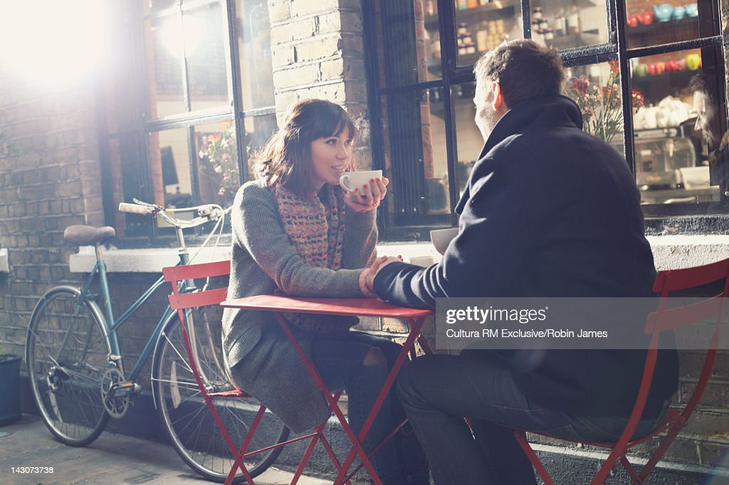 Couple having coffee at sidewalk cafe : Stock Photo