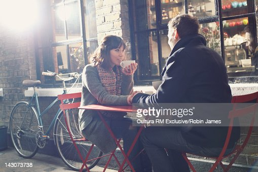 Couple having coffee at sidewalk cafe