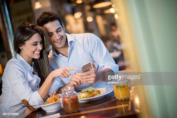 Couple having dinner and looking at a mobile phone