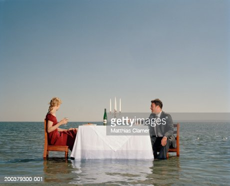 Couple having dinner in middle of ocean, side view : Stock Photo