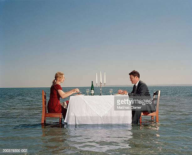 Couple having dinner in middle of ocean, side view