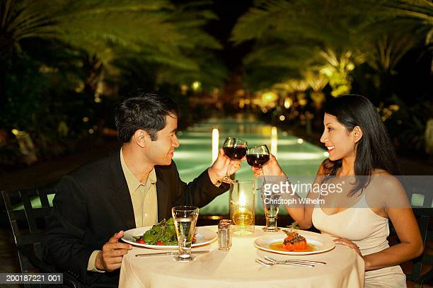 Couple having dinner outdoors, toasting glasses, side view