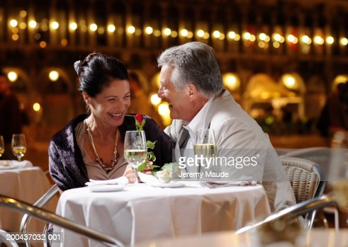 Couple having drinks at restaurant in square, smiling, night : Photo