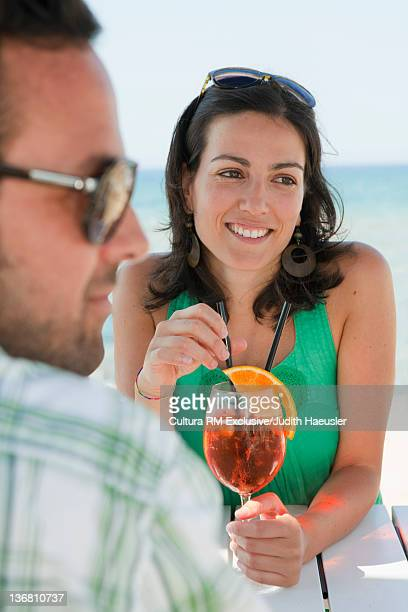 Couple having drinks at table outdoors