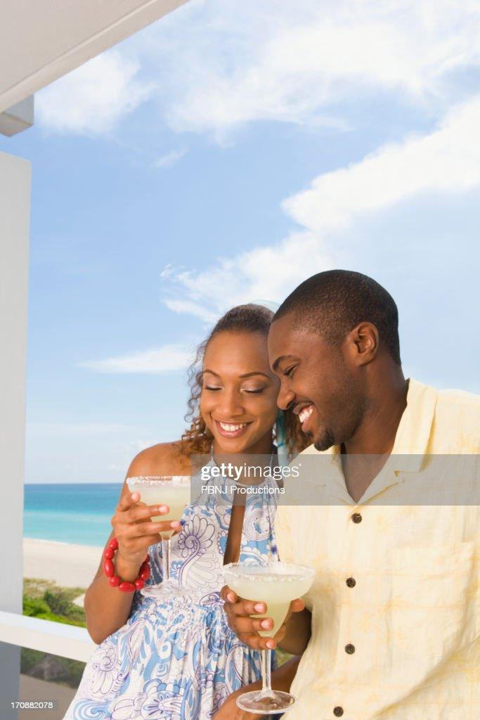 Couple having drinks on balcony : Stock Photo
