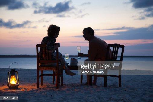 Couple Having Drinks On Beach At Sunset Zanzibar Stock Photo