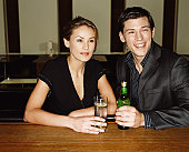 Couple having drinks, resting arms on bar