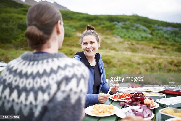 Couple having food at table on mountain