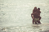 Copy space shot of a young man giving his girlfriend a piggyback ride in the shallow water.