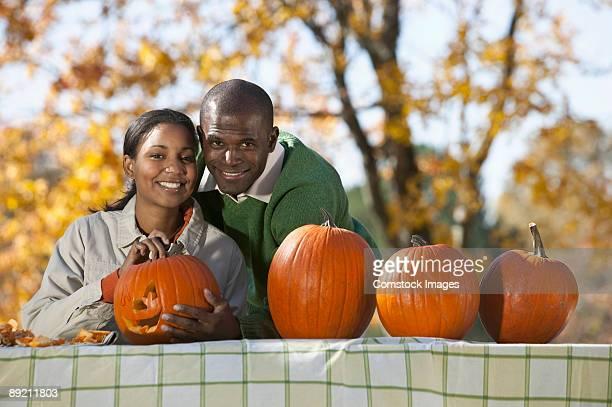 Couple having fun carving pumpkins outdoors.