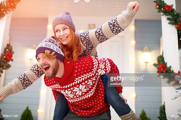 Couple having fun in front of house.