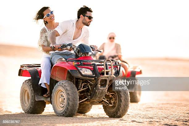 Couple having fun on quad bike.