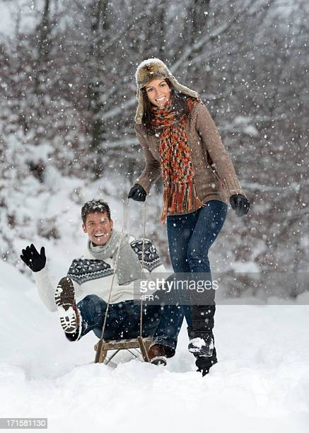 Couple having Fun on Sled in a Snowstorm