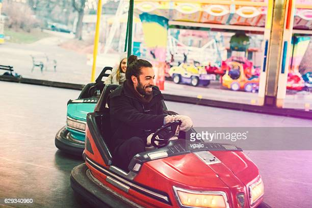 Couple Having Fun Riding Bumper Cars.
