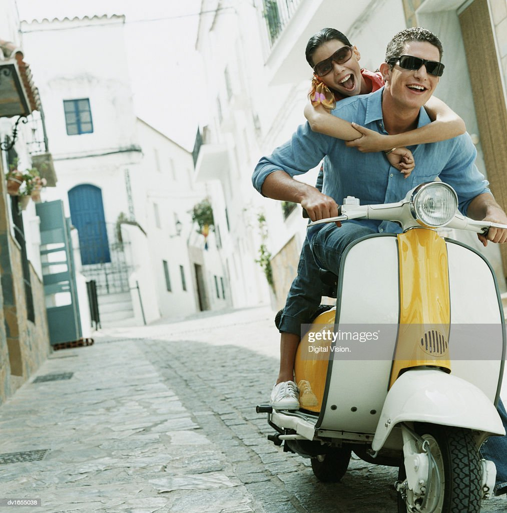 Couple Having Fun Riding on a Motor Scooter Through an Alley : Stock Photo