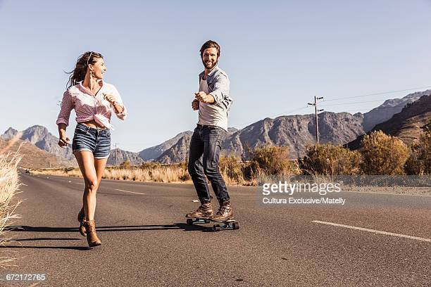 Couple having fun using skateboard on mountain road, Franchook, South Africa