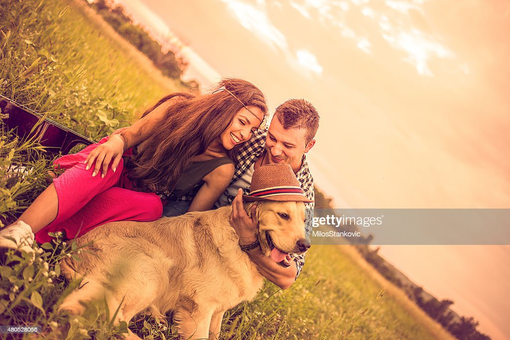 Couple having fun with dog in nature : Stock Photo