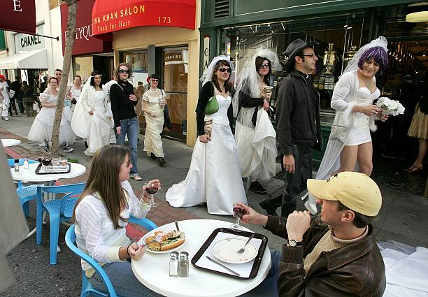 A couple having lunch at an outdoor cafe looks on as a flash mob group calling