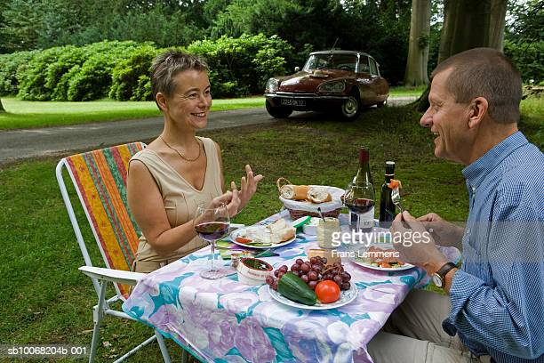 Couple having picnic, eating food, side view