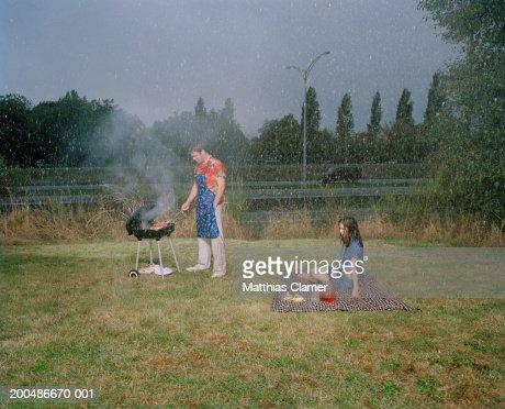 Couple having picnic in rain, man grilling : Stock Photo