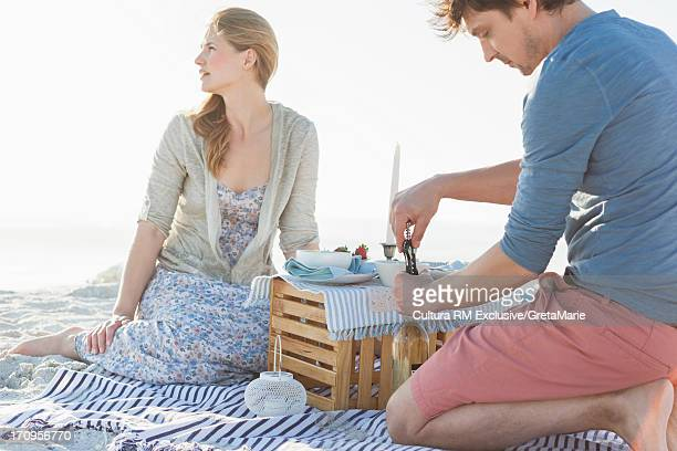 Couple having picnic on beach, man opening bottle of wine