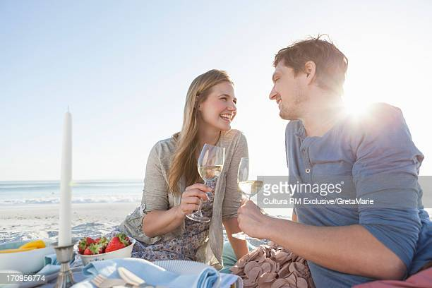 Couple having picnic on beach with wine