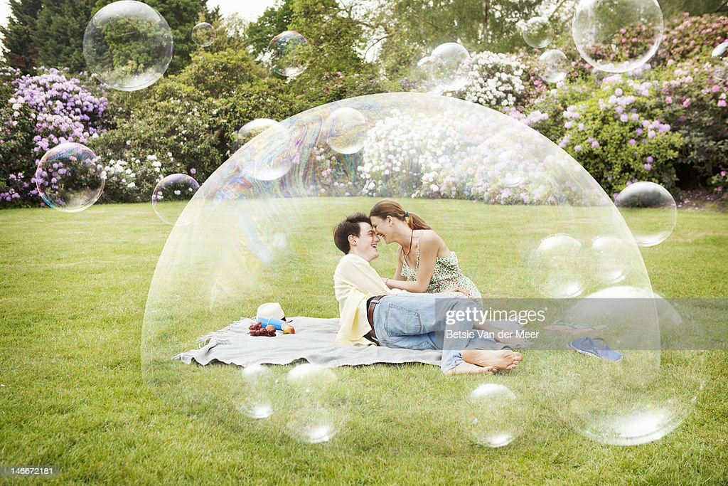 Couple having picnic surrounded by bubbles. : Stock Photo